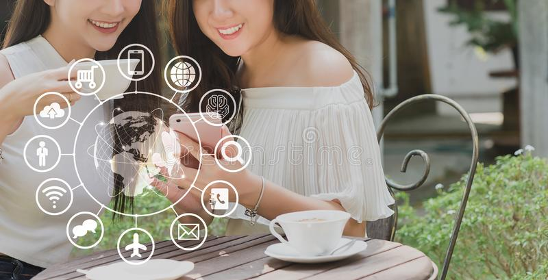 Dwa nastoletniej kobiety u?ywaj? smartphone z technologii ikon?, internet zdjęcie royalty free