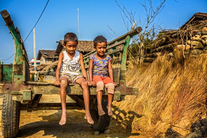 Dwa nepalese chłopiec siedzi na drewnianej furze w Nepal zdjęcia royalty free