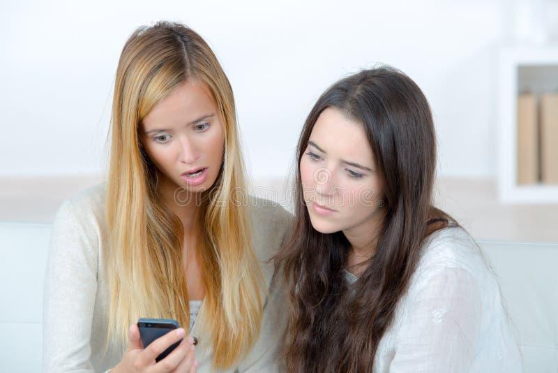 Dwa nieradej młodej kobiety patrzeje telefon komórkowego obrazy stock