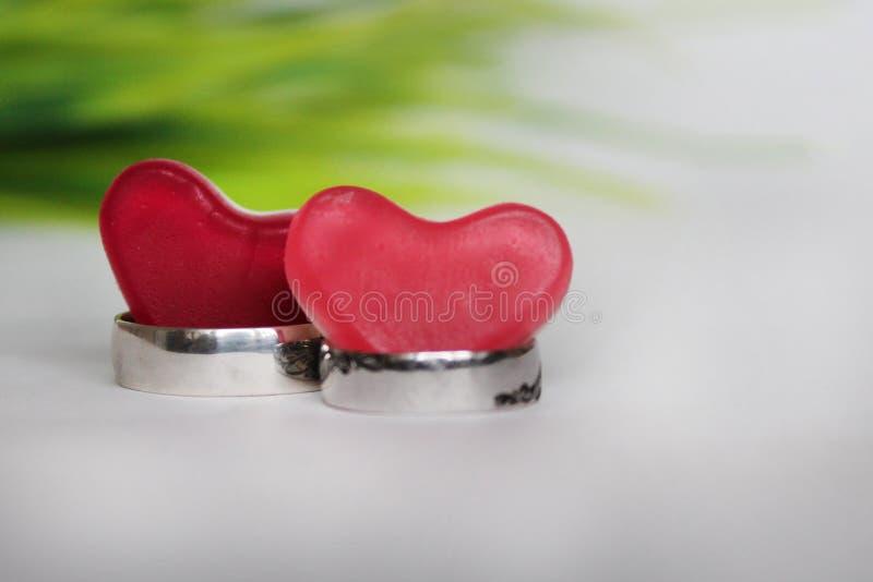 Dwa obrączki ślubnej i dwa czerwonego serca na tle zielona trawa zdjęcia stock