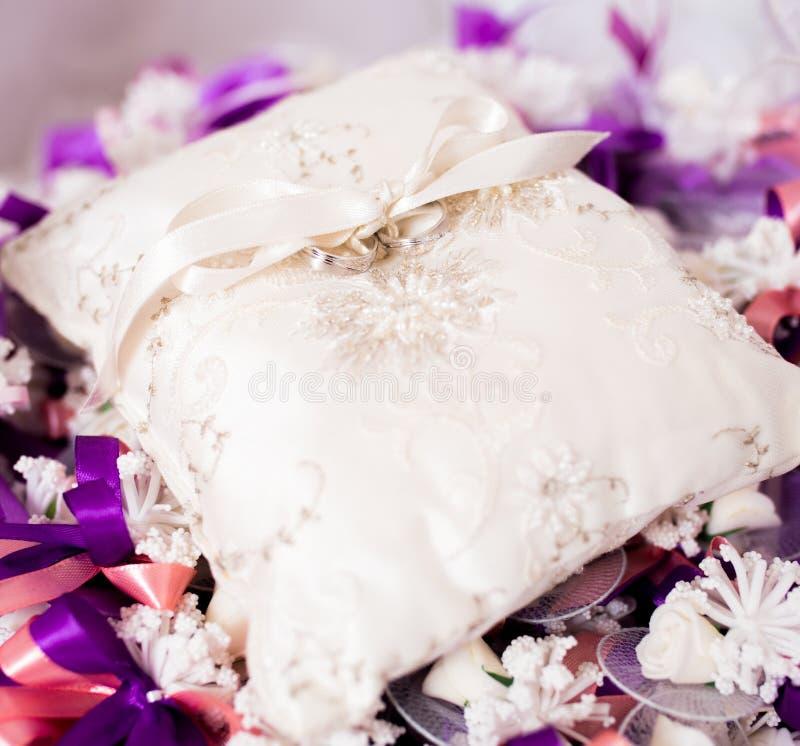 Dwa obrączki ślubnej na białej dekoracyjnej poduszce zdjęcia stock