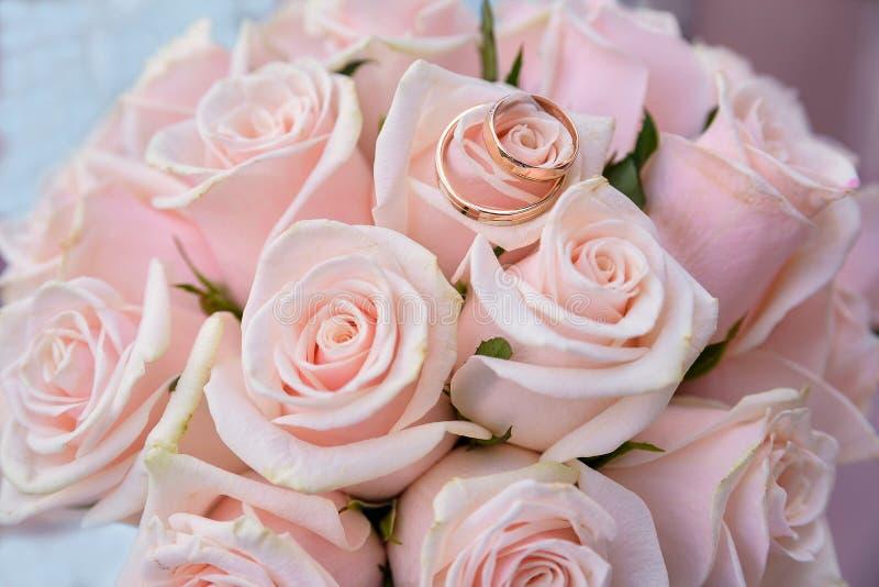 Dwa obrączki ślubnej na kolorowym bukiecie różowią róże, zamykają w górę zdjęcia stock