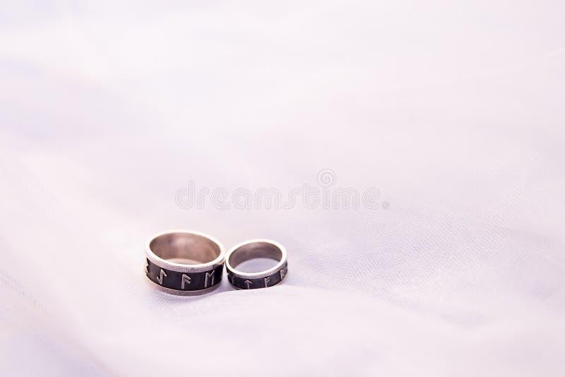 Dwa obrączki ślubnej osrebrzają na białym tle z kopii przestrzenią pierścionki z runes Poj?cie mi?o?? i ma??e?stwo fotografia royalty free