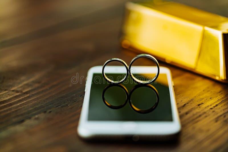 Dwa obrączki ślubnej są na telefonu pokazie Para złociści pierścionki jest na tle drewniany stół w pokoju zdjęcia stock