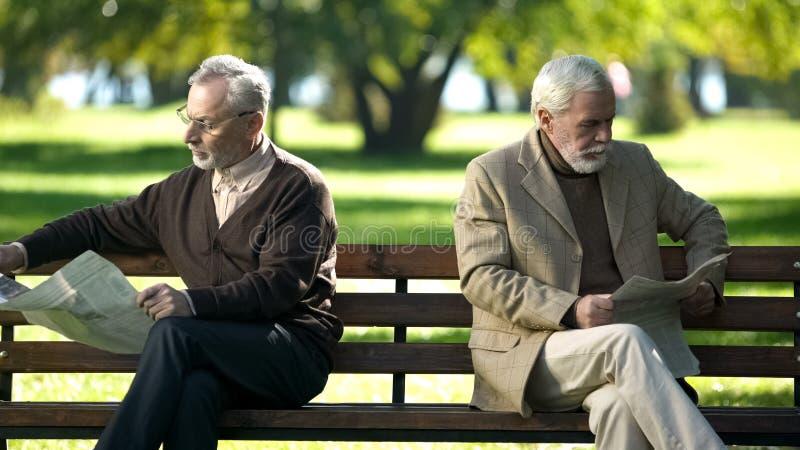 Dwa obra?ali starych cz?owieków czyta gazety, siedzi na ?awce w parku, be?t zdjęcia stock