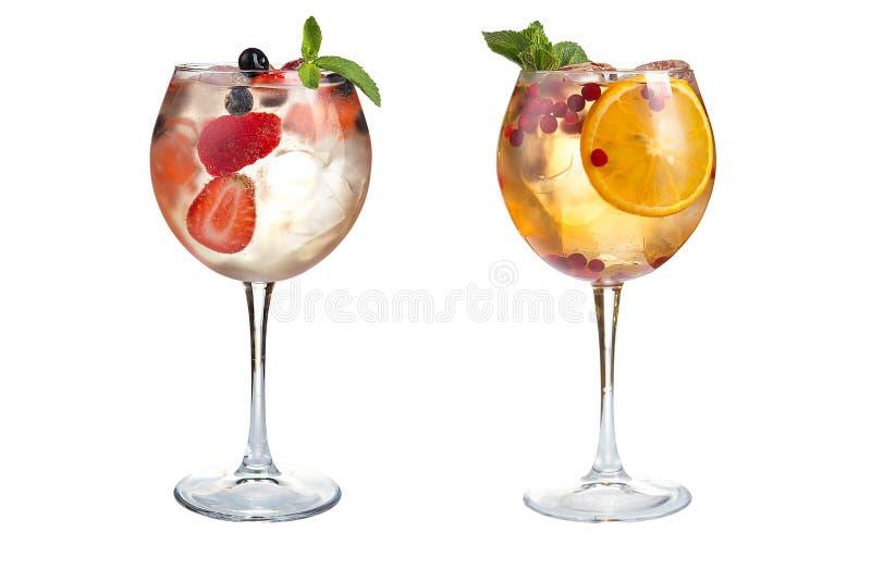 Dwa odświeżająca alkoholiczka lub bezalkoholowi koktajle z mennicą, owoc i jagodami na białym tle, Koktajle w szklanych czara zdjęcia stock