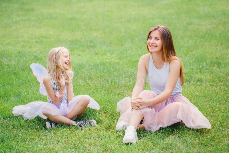Dwa one uśmiechają się śmiesznej Kaukaskiej dziewczyny siostry jest ubranym różowego spódniczka baletnicy tiul omijają w parkowej fotografia stock