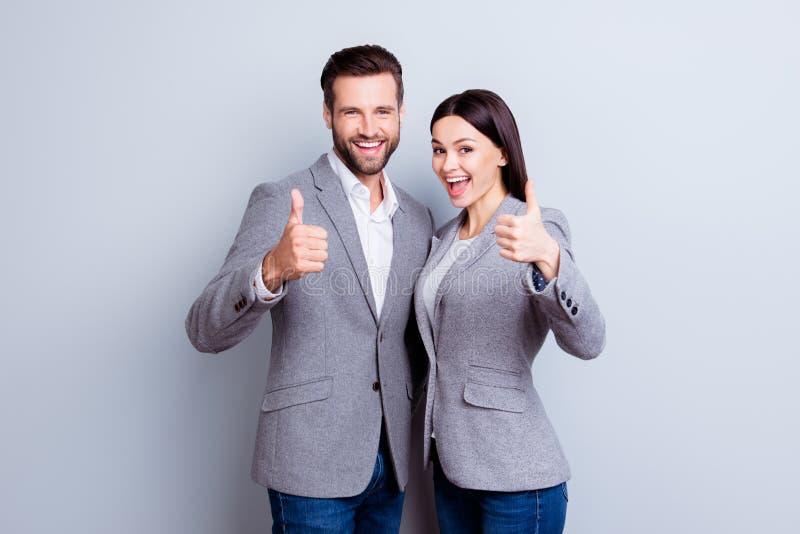Dwa one uśmiechają się szczęśliwego biznesmena w formalwear pokazuje aprobaty zdjęcie stock