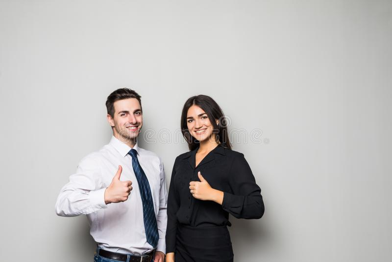Dwa one uśmiechają się szczęśliwego biznesmena w formalwear pokazuje aprobaty na szarość zdjęcie royalty free
