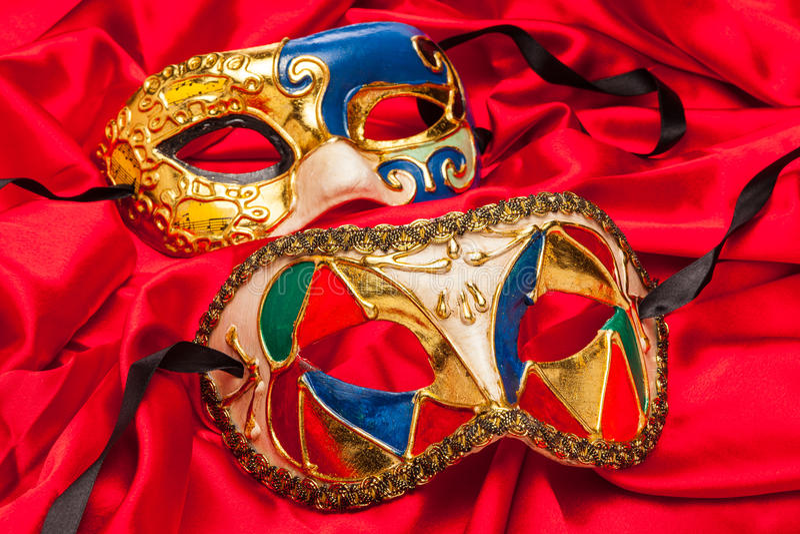 Dwa ostatki maski na czerwonym jedwabiu zdjęcie stock