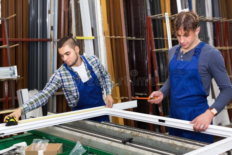 Dwa ostrożnego pracownika sprawdza okno zdjęcie royalty free