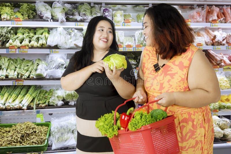 Dwa otyłej kobiety kupuje organicznie warzywa fotografia stock