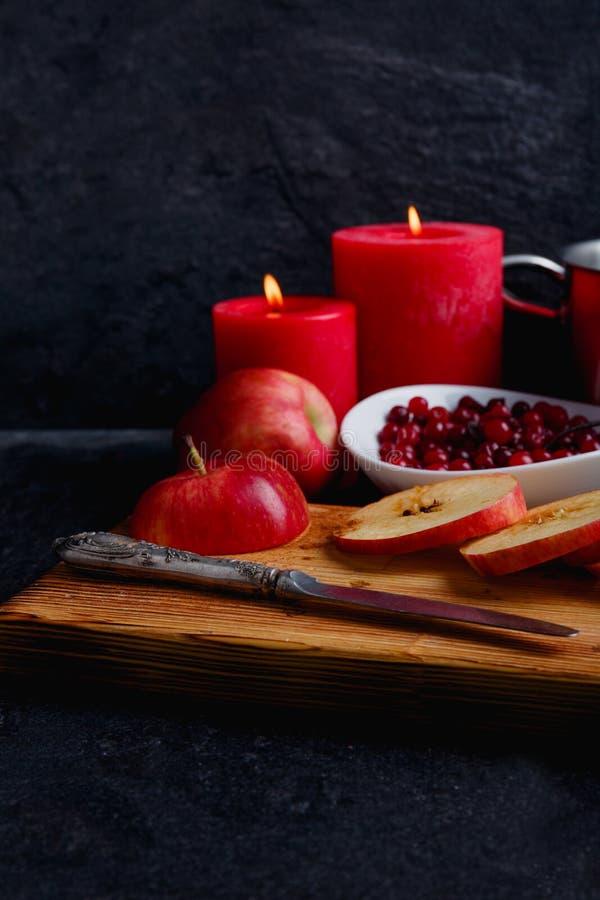 Dwa płonącej czerwonej świeczki, deska z pokrojonymi jabłkami i głęboki bielu talerz z cranberries, Boczny widok zdjęcia royalty free