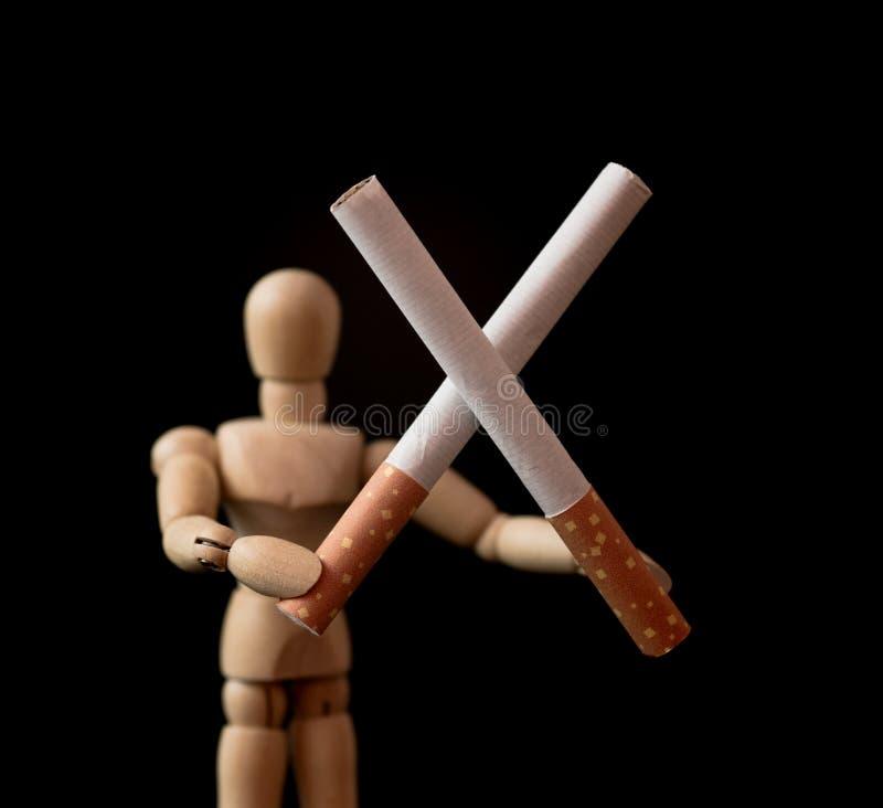 Dwa papierosu w krzyż formy mieniu drewnianą mężczyzna postacią, ` skwitowany, ty możesz robić mu ` pojęcie obrazy stock