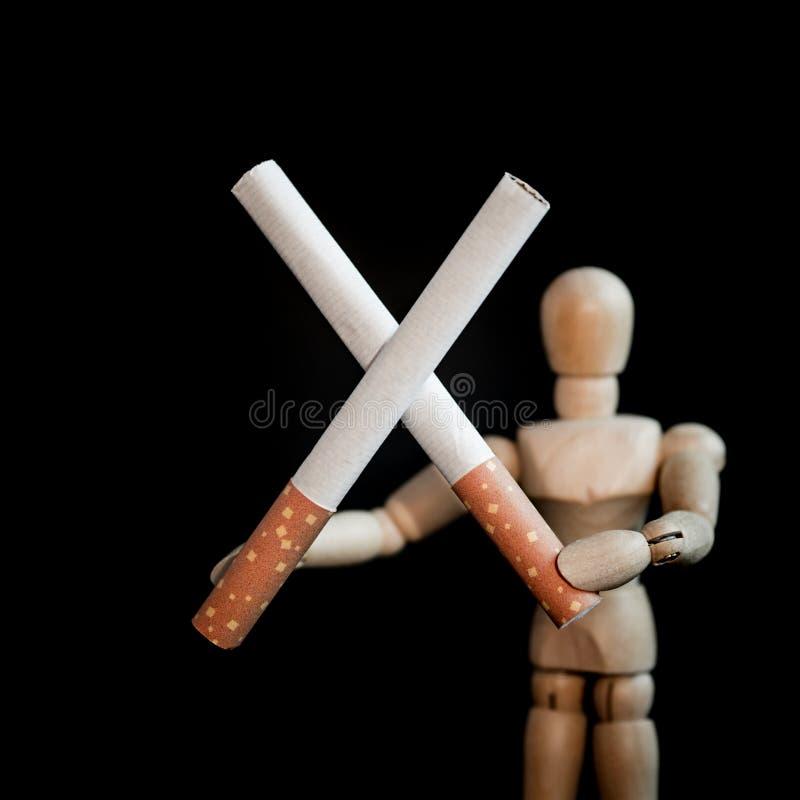 Dwa papierosu w krzyż formy mieniu drewnianą mężczyzna postacią, ` skwitowany, ty możesz robić mu ` pojęcie obrazy royalty free