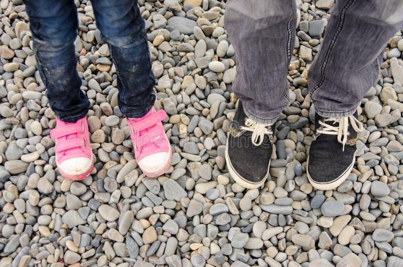 Dwa pary cieki w sneakers dorosli i dzieci, są na otoczaku obrazy royalty free