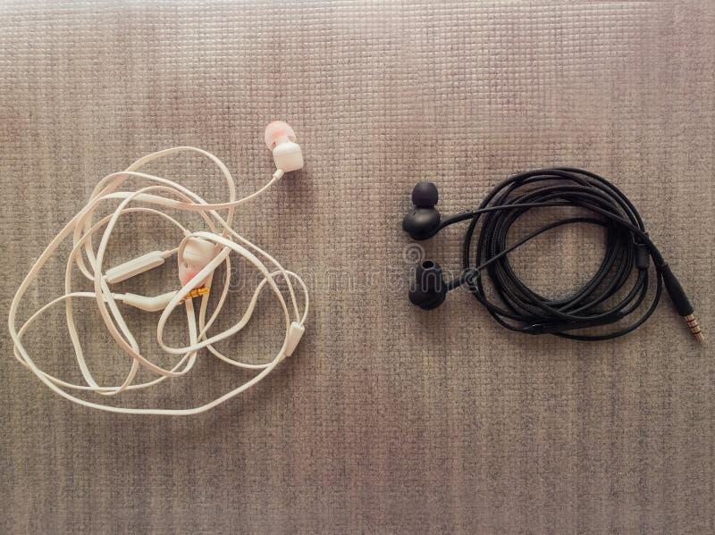 Dwa pary czarny i biały depeszujący hełmofony dla muzycznego słuchania, Zawija innych sposoby, jeden czochra podczas gdy inny sta obrazy stock