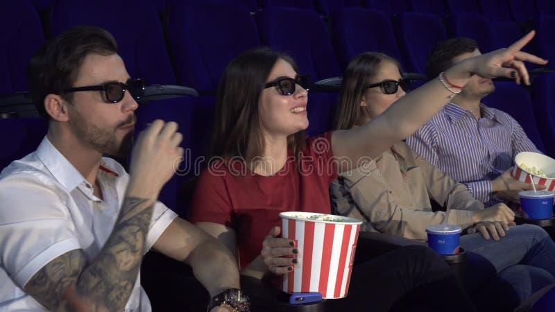 Dwa pary siedzą w kinie i jedzą popkorn zdjęcia stock