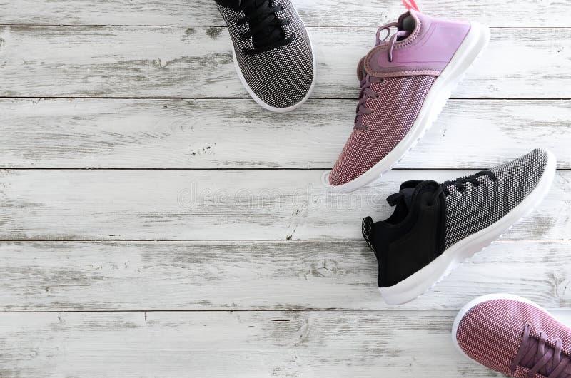 Dwa pary sneakers fiołek, czarny i biały na drewnianym backg zdjęcia stock