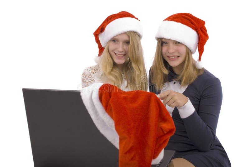 Dwa piękna blondynka w Santa Claus kapeluszu z laptopem obrazy royalty free