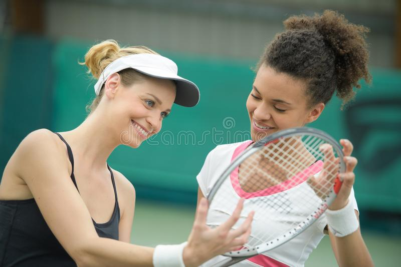Dwa pięknego żeńskiego gracz w tenisa trzyma kanta ono uśmiecha się fotografia stock