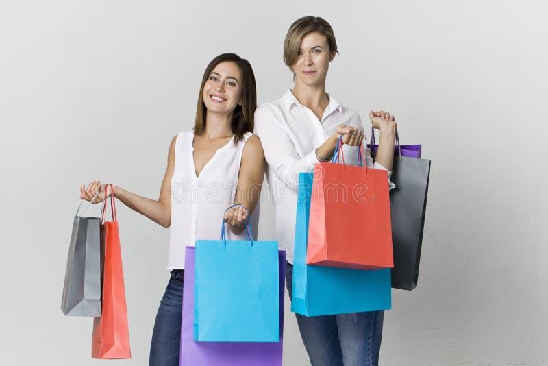 Dwa pięknego żeńskiego przyjaciela na zakupy z kolorowymi torbami zbyt obraz royalty free