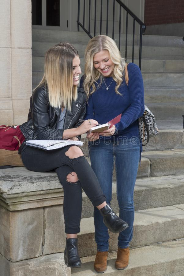 Dwa pięknego młodego żeńskiego ucznia wpólnie na kampusie obrazy stock