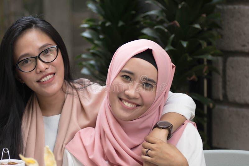 Dwa pięknej azjatykciej kobiety patrzeje kamerę podczas gdy ściskać each obrazy royalty free