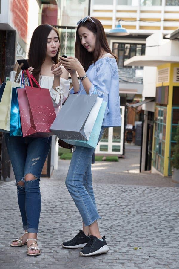dwa pięknej azjatykciej shopaholic kobiety z smartphone i colorfu obraz royalty free