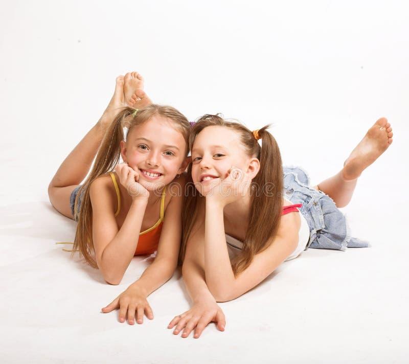 Dwa pięknej dziewczyny kłaść na bielu zdjęcia stock