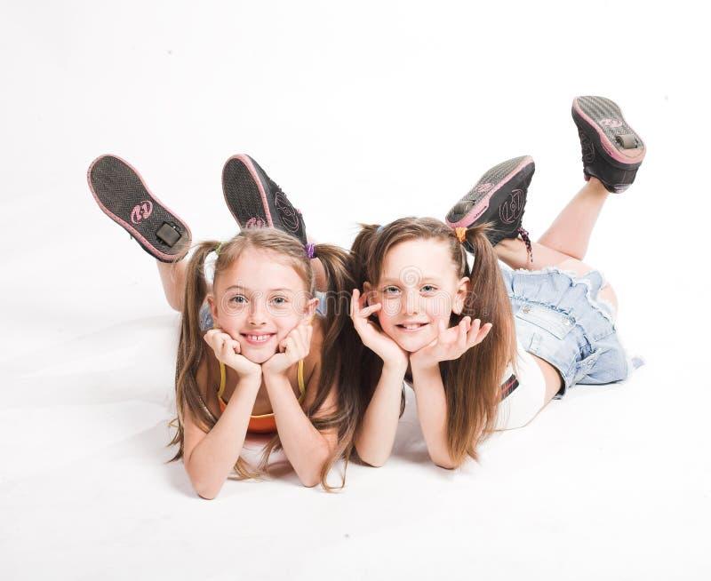 Dwa pięknej dziewczyny kłaść na bielu fotografia stock