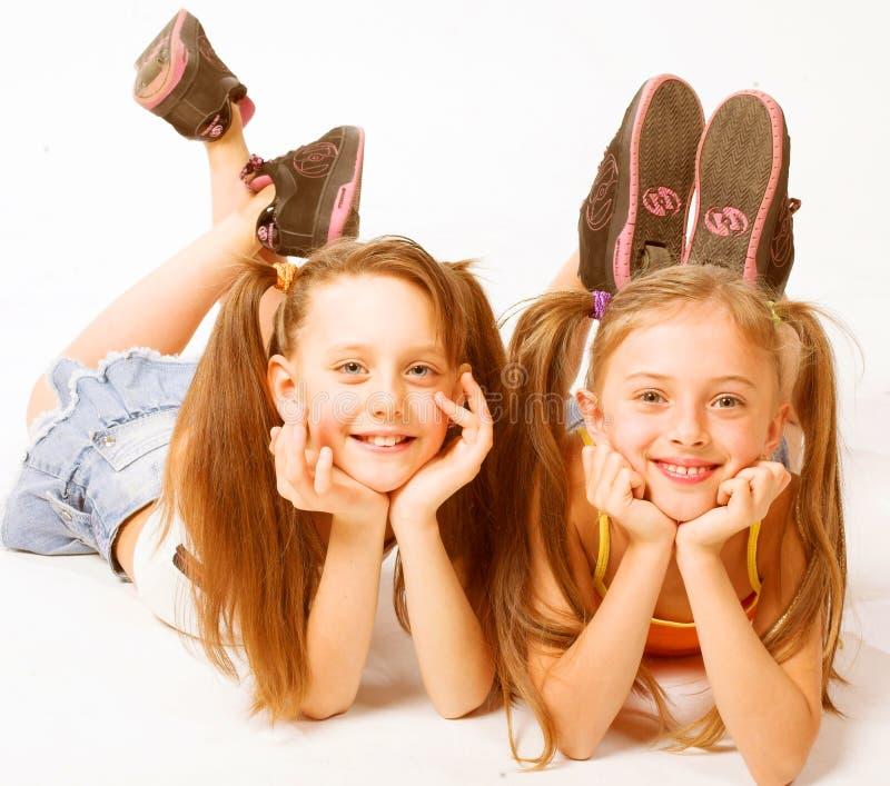 Dwa pięknej dziewczyny kłaść na bielu obraz stock