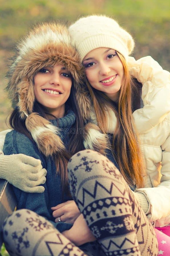 Dwa pięknej dziewczyny siedzi na ławce w jesieni zdjęcie stock