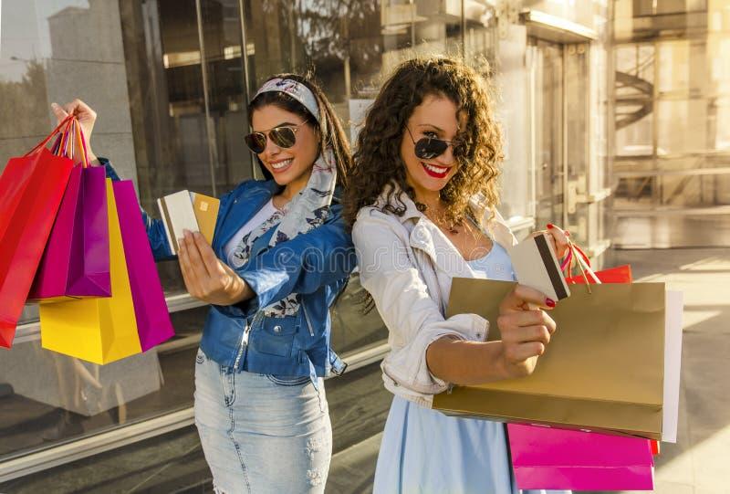 Dwa pięknej dziewczyny trzyma kredytowe karty przed kamerą, zdjęcie royalty free