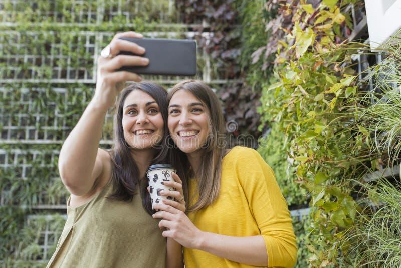 Dwa pięknej kobiety bierze selfie z telefonem komórkowym Jeden trzyma filiżanka kawy Są roześmiani Outdoors styl życia i zdjęcia royalty free