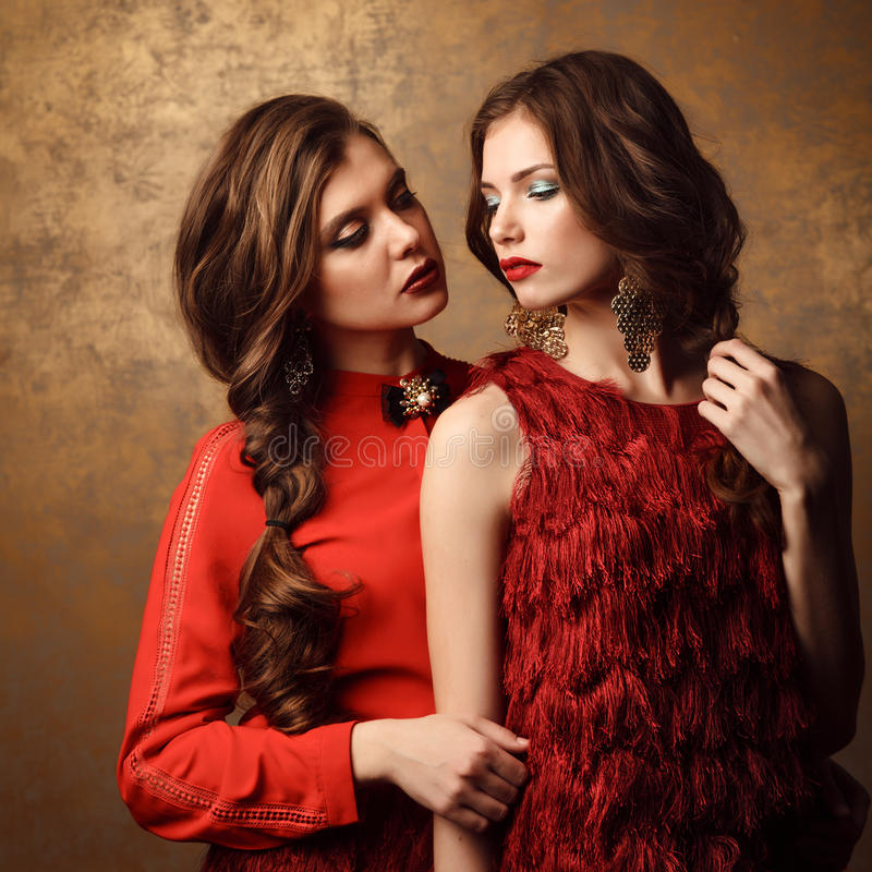 Dwa pięknej kobiety w czerwonych sukniach Perfect fryzura i makeup obrazy royalty free