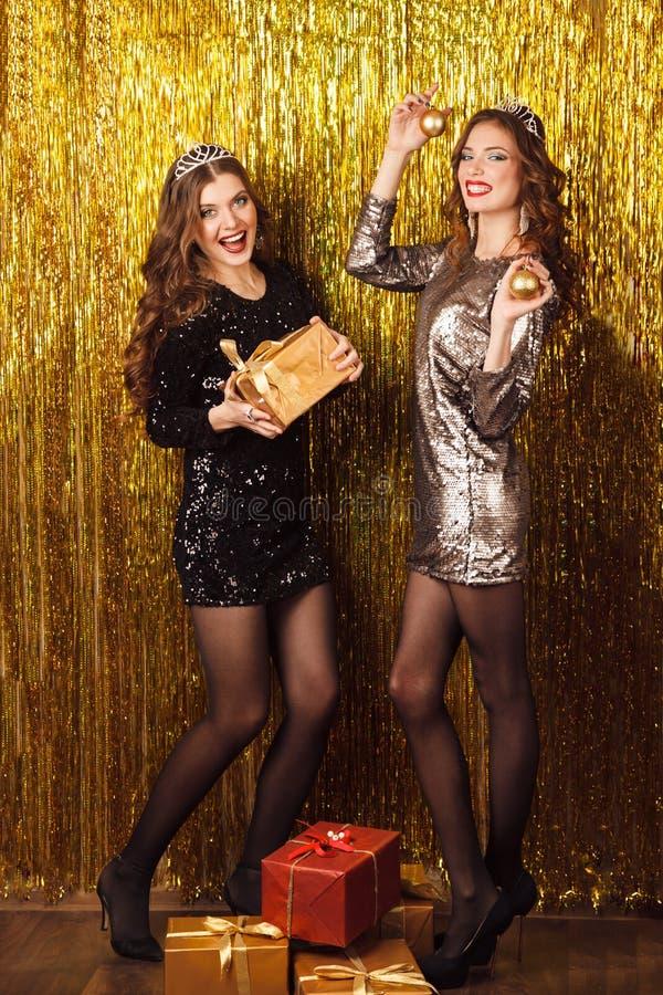 Dwa pięknej kobiety w przyjęciu gwiazdkowym na iskrzastym tle obrazy royalty free