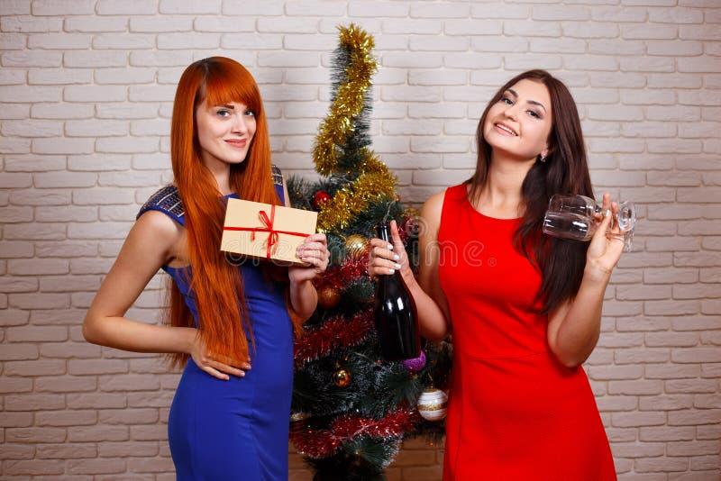 Dwa pięknej kobiety w wieczór są ubranym bawić się z prezenta pudełkiem, gl zdjęcia royalty free