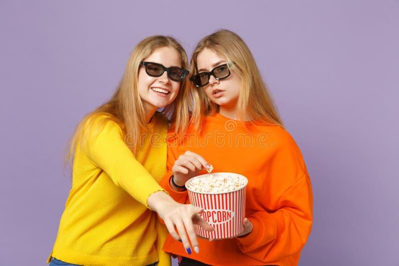 Dwa pięknej młodej blondynka bliźniaków siostr dziewczyny ogląda filmu film w 3d imax szkłach, trzyma popkorn dalej obrazy stock