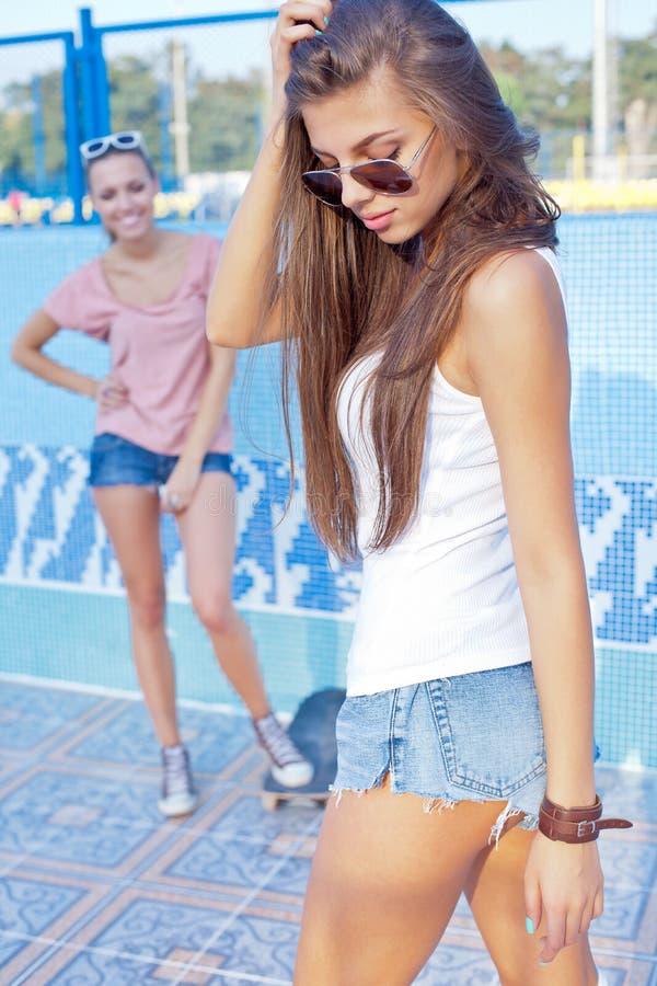Dwa pięknej młodej dziewczyny na podłoga pusty basen fotografia stock