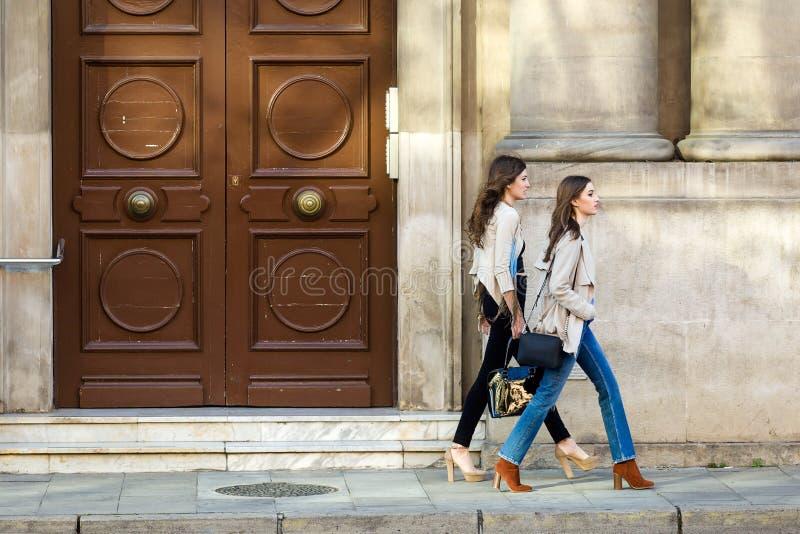 Dwa pięknej młodej kobiety chodzi i opowiada w ulicie fotografia royalty free