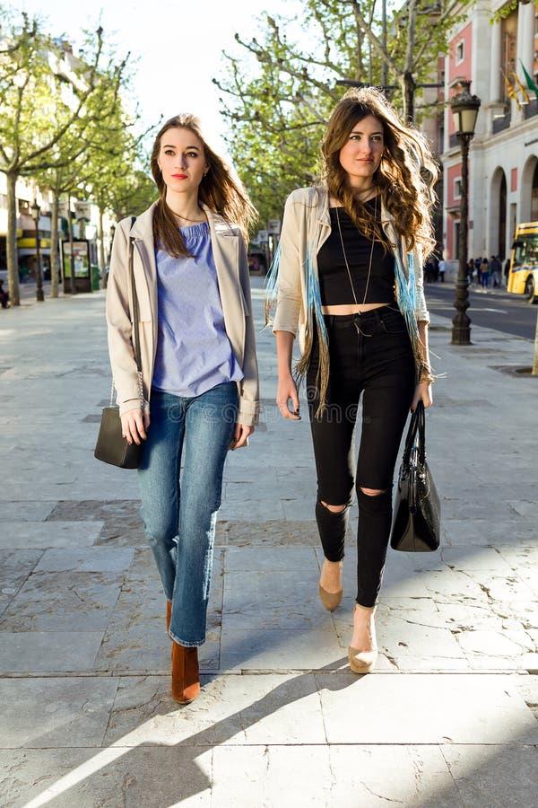 Dwa pięknej młodej kobiety chodzi i opowiada w ulicie zdjęcia stock