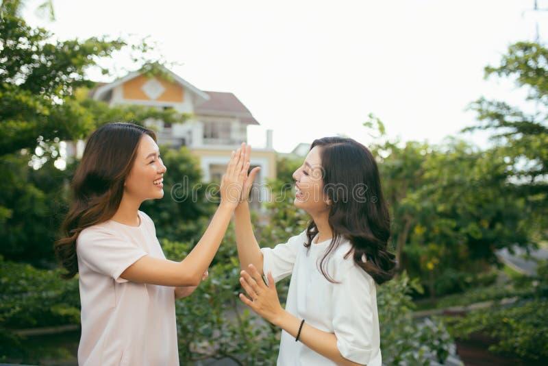 Dwa pięknej młodej kobiety daje wysokości pięć - Ładne dziewczyny standi fotografia stock