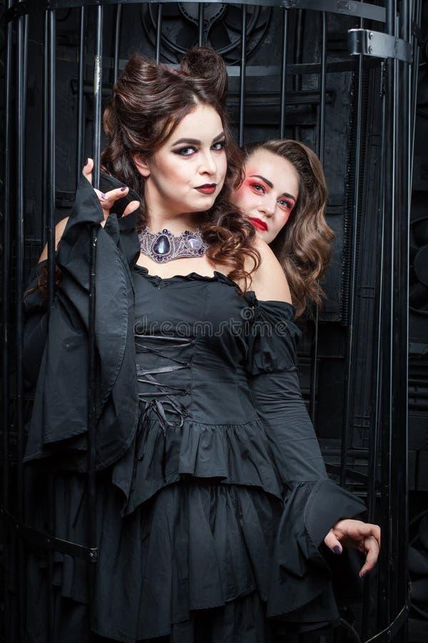Dwa pięknej młodej kobiety w czarnych sukniach zdjęcie royalty free