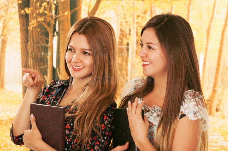 Dwa pięknej młodej szkoły wyższa dziewczyny nad spadkiem obrazy royalty free