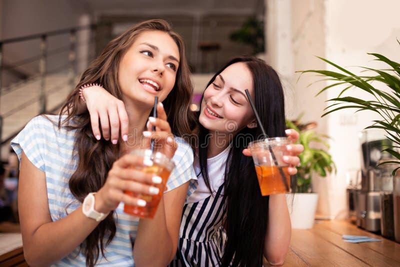 Dwa pięknej młodocianej uśmiechniętej dziewczyny z ciemnym włosy, ubierającym w przypadkowym stroju, ściskają each inny w wygodny obrazy royalty free