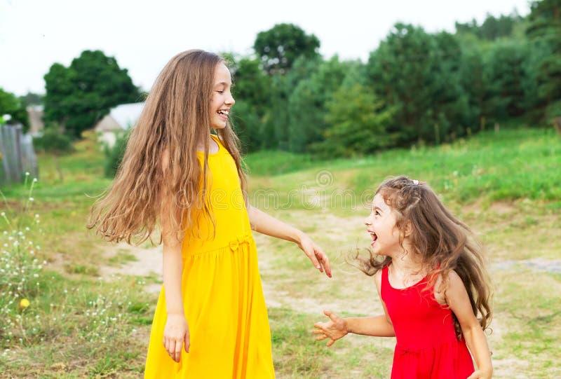 Dwa pięknej małej dziewczynki bawić się i ono uśmiecha się przy pogodnym lato d fotografia stock