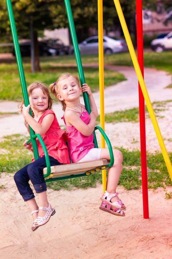 Dwa pięknej małej dziewczynki na huśtawki plenerowe w boisku zdjęcie royalty free
