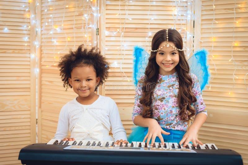 Dwa pięknej małej dziewczynki w świątecznych ubiorach bawić się pianino na wakacyjnym przyjęciu fotografia royalty free