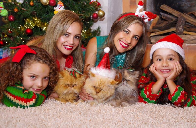 Dwa pięknej mamy z jej małymi dziewczynkami, być ubranym boże narodzenia odziewają kędzierzawa dziewczyna z czerwonym krawatem w  fotografia stock
